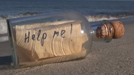 perdido : Seascape with transparent bottle with a message help me in the sand