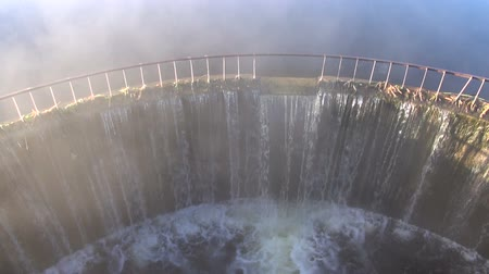manmade : Water flowing through dam with fog rising in the morning