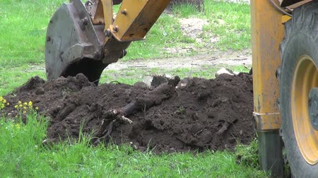 kalhoty : Industrial  excavator digging a hole on lawn with worker wearing black trousers walking by