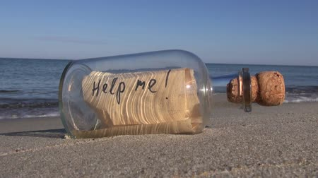 perdido : Seascape with transparent vintage bottle with a message help me in the sand
