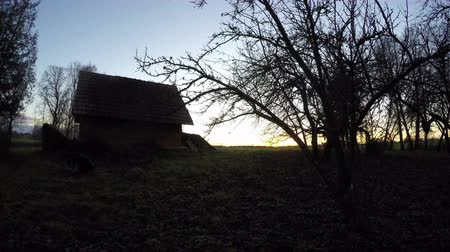 ahır : Landscape with old desolate clay barn and sun rising over rural fields in the autumn, time lapse 4K Stok Video