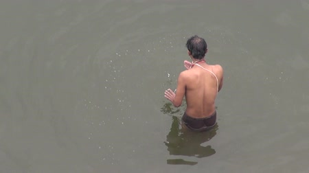 ascetic : Spiritual ablutions of solitary Brahman in morning in Varanasi, sacred Hinduism Ganges river, India