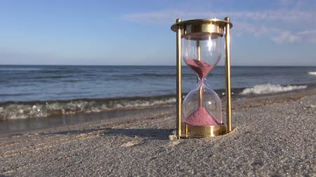 ampulheta : Hourglass sandglass with pink sand on the beach by the sea on sunny evening Vídeos