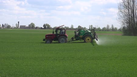 pasture land : Tractor with reservoir of chemicals spraying green young wheat field in early spring