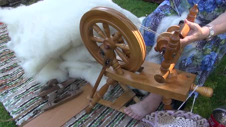 příze : Woman spinning wool into yarn with spinning wheel outdoors during medieval fair