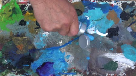 pallette : Painter squeezing blue paint out of tube and mixing it