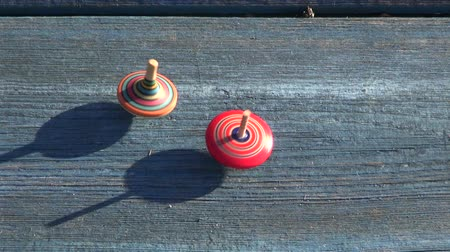 toy : Two multicolored sunlit wooden spins spinning on wooden background Stock Footage