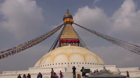 bodhnath : KATHMANDU, NEPAL - CIRCA DECEMBER 2013: People walk around the Buddhist spiritual center Boudhanath Stupa. Boudhanath is a UNESCO world heritage site. Buddha eyes on stupa.