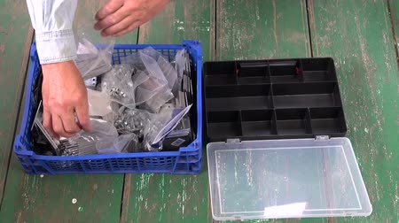toolbox : worker sorting nails in new plastic box
