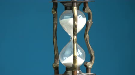hora : Rotating on blue background vintage brass hourglass sandglass and sand motion, 4K
