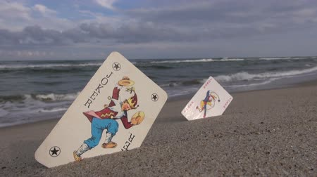hamis : Two playing cards jokers on beach sand near summer sea