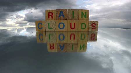 гимназия : Alphabetical wooden cubes toys on mirror with word Rain Clouds, time lapse 4K