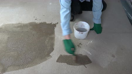 мастер на все руки : Worker with paintbrush priming concrete floor protection primer in new room Стоковые видеозаписи