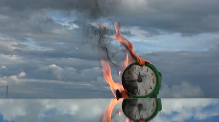 язык : Burning  old retro green alarm clock face on mirror in space. Time and fire concept