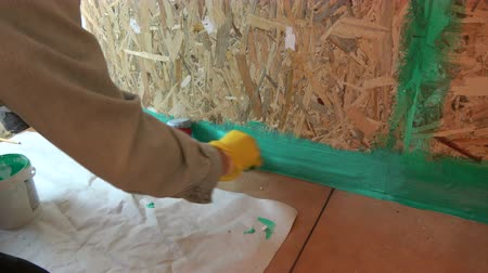encanador : Worker with small paintbrush waterproofing wooden  bathroom construction Stock Footage