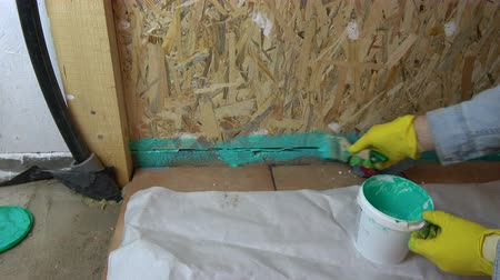 fikstür : Worker with paintbrush waterproofing wooden  bathroom construction Stok Video