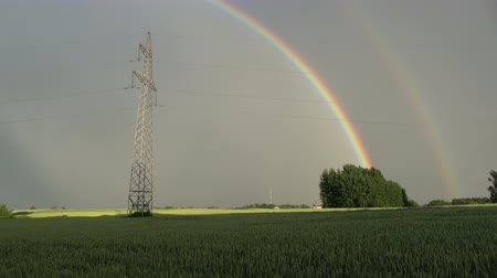szépen : Beautiful  evening rainbow over farmland fields with electricity tower Stock mozgókép