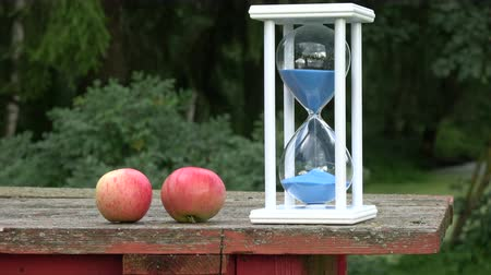 sandálias : Summer end still-life with blue hourglass sandglass and two apples in old table in garden