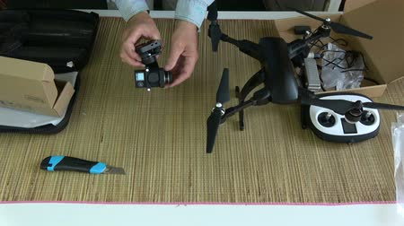 fixing : Videographer photographer testing new foldable drone gimbal with action camera Stock Footage