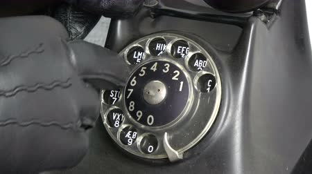 hívó : Gangster thief hand with black leather glove dialing old phone telephone dial disc