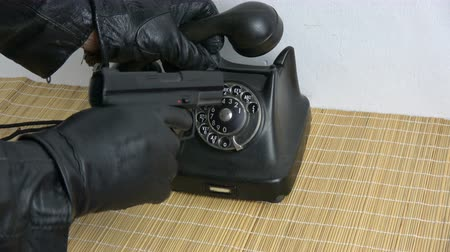 банда : Gangster thief hand with leather glove dialing ancient telephone dial disc with hand gun pistol
