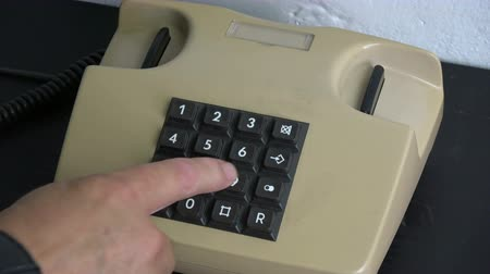numerais : Man finger pressing numbers buttons on classic retro phone telephone on black wooden table