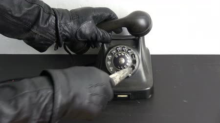 housebreaking : Gangster thief hand with black leather glove dialing ancient telephone dial disc with vintage dagger gun Stock Footage