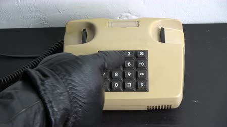 hívó : Robber gangster hand with black leather glove pressing numbers buttons on classic retro old phone telephone Stock mozgókép