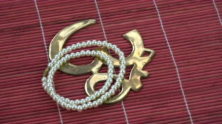sanskrit : Rotating indian pearls necklace and OM sign symbol on red bamboo mat Stock Footage