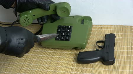 hívó : Robber gangster hand with black  glove and dagger gun  pressing numbers buttons on  retro old green phone telephone Stock mozgókép