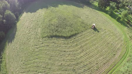 mow : old tractor cut haying grass from summer meadow in farm, aerial view