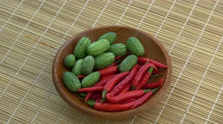 mexicano : Rotating in wooden plate chili peppers and mouse melons Melothria scabra