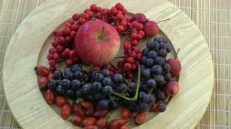 üvez ağacı : Rotating in wooden plate northern grapes, wild rose hips,apples and rowan berries on bamboo mat