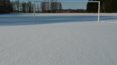 цели : In small winter stadium drone flying through football gate