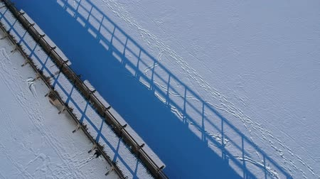 январь : Wooden bridge with blue shadow on snowy winter lake ice, aerial view