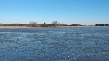 frozen lake : Drone fly above cracked spring time lake ice, aerial view