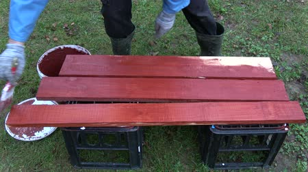 yarda : Worker paint wooden planks in red