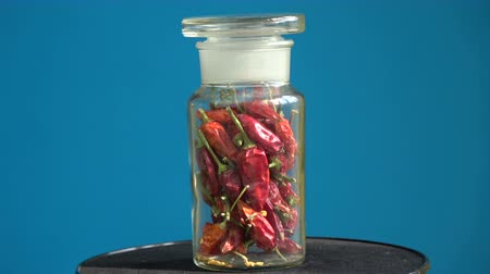 hot peppers : Rotating glass pot with dry red hot chili peppers Stock Footage