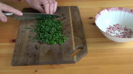 нарезки : Cut  green onions on wooden cutting board on table Стоковые видеозаписи