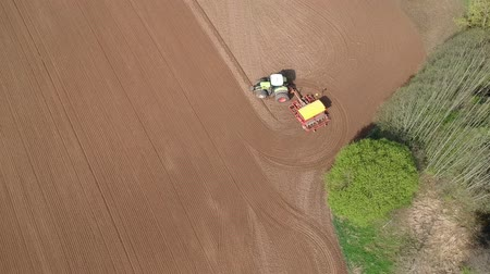 tırmık : Agriculture tractor sowing crop on spring  field near grove, aerial view
