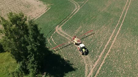 herbicides : Farm tractor in early spring spraying  crop field, aerial view