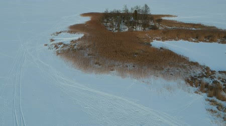 kamış : Drone above snowy lake ice and island in midwinter, aerial view