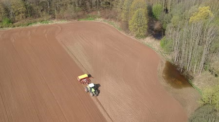 plowed land : tractor sowing crop on spring farmland field, aerial view