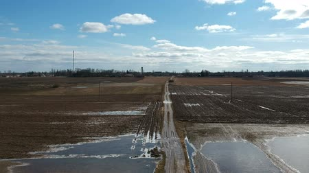 Bad early spring time farmland road with water puddle, aerial view Stockvideo