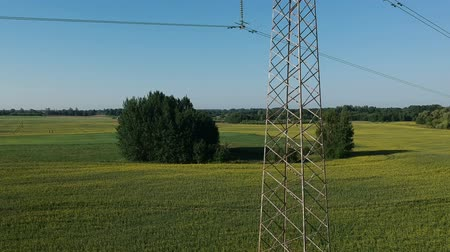 voltů : Drone fly up height near big electricity tower on farmland field, aerial