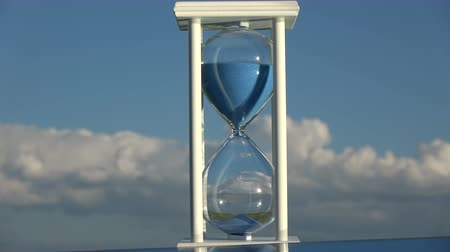 medir : Hourglass sandglass on sky background and blue sand motion