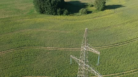 powerline : Drone fall away landing near high electricity tower on farm field, aerial view