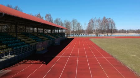 トラック : Athletic running track with line and tribune in small stadium in spring, aerial view