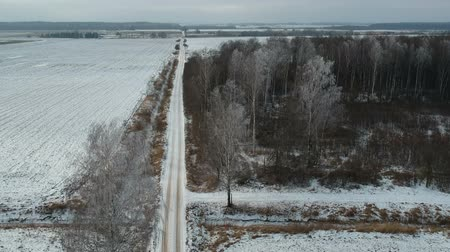 Midwinter rural road with snow and forest with hoarfrost, aerial view