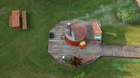 Outdoor bathhouse with hot water tub in yard, aerial view Stockvideo
